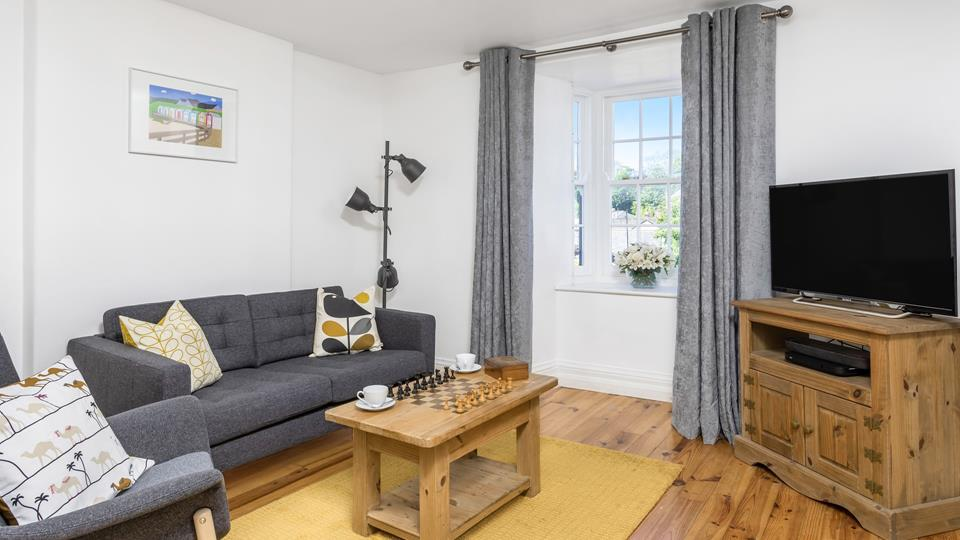 The sitting room has a beautiful bay window, natural wood floors, a textile sofa and armchair with solid natural wood coffee table and TV unit.