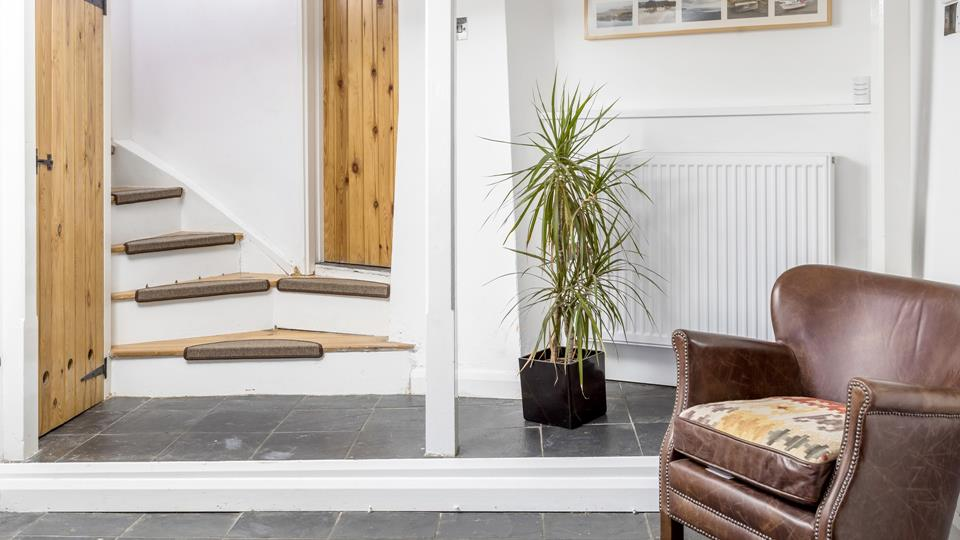 The ground floor has a natural slate tiled floor with an under stairs cupboard to the left with the washing machine/dryer and two steps up to the shower room.