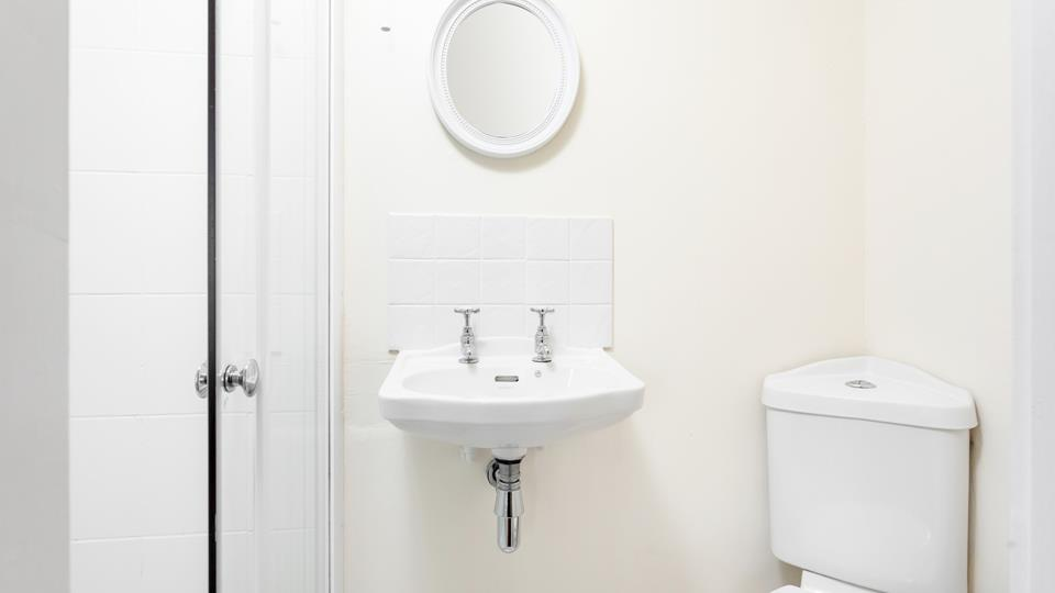 Bedroom three has an en suite shower room with a corner WC and small hand basin with mirror above.