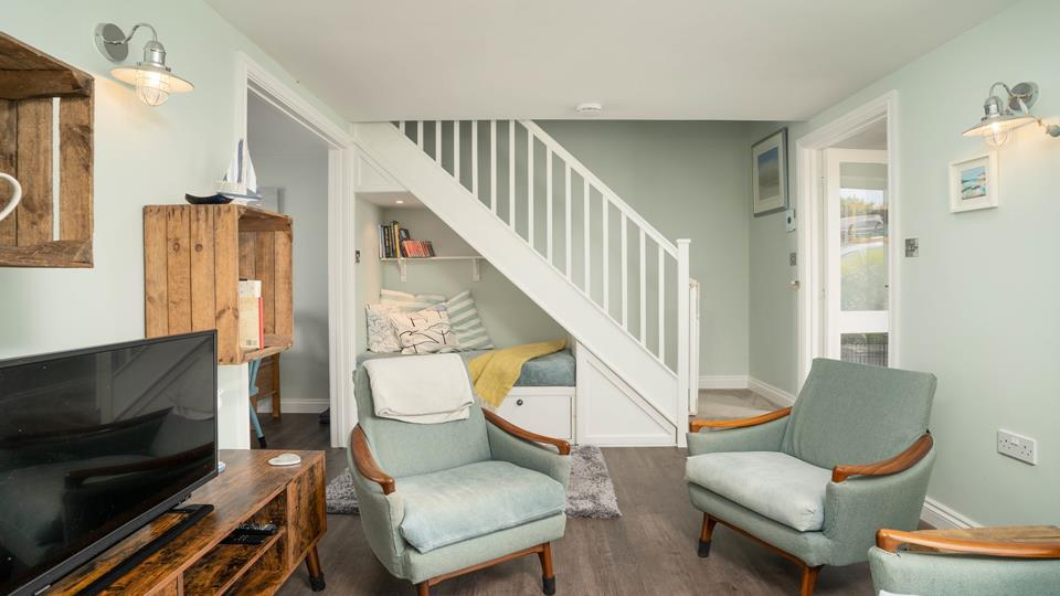 The sitting-room is made for relaxing. Stairs take you up to the first floor bedrooms and family shower room.