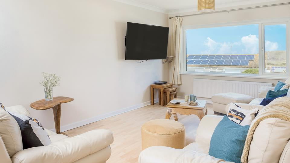 """There is a large 62"""" Smart TV in the sitting room which is light and airy, plenty of natural wood occasional tables are perfect for drinks and snacks."""