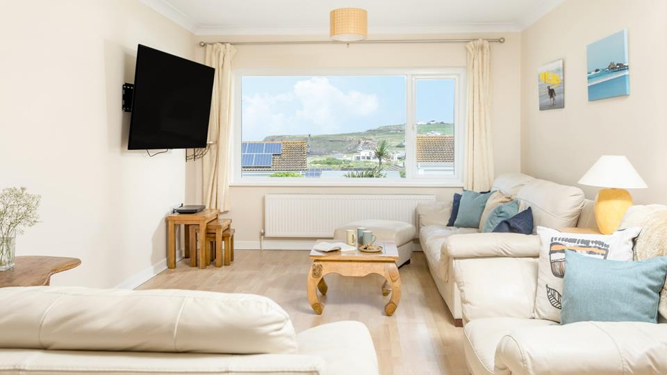 """Stunning views over Widemouth Bay beach from the sitting room, enjoy the 62"""" Smart TV whilst snuggled in the comfy cream leather sofas and armchair."""