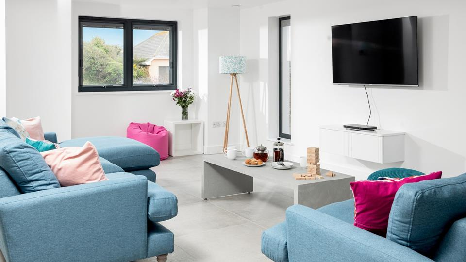 The sitting room area in the living space has a ceramic tiles floor a wall mounted Smart TV, contemporary coffee table and bespoke standard lamp with fish art shade.