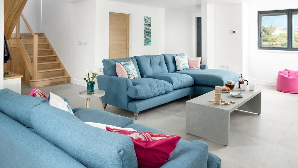 The living space is open plan and has a textile contemporary L-shaped sofa and further textile sofa with accent bean bags. The mood lighting on the internal stairwell enhances the shape and dimension.